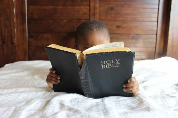 photo of child reading holy bible